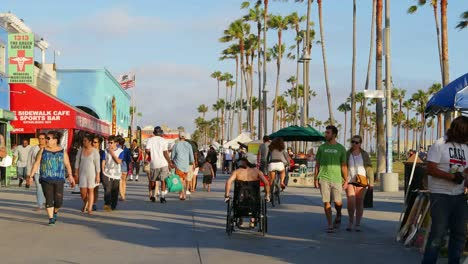 Los-Angeles-Venice-Beach-Boardwalk-Visitors-Walk-Past-Shops-With-Flags