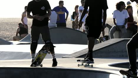 Los-Angeles-Venice-Beach-Skater-Hesitates-Amongst-Others-With-Beach-Beyond