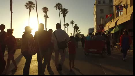 Los-Angeles-Venice-Beach-Walking-Down-Boardwalk-With-Sun-Behind-Palms