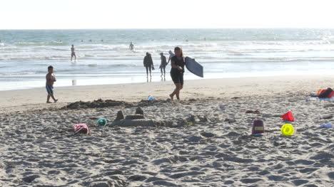 Los-Angeles-Venice-Beach-Woman-And-Boy-Walk-Past-Sandcastle-Remains