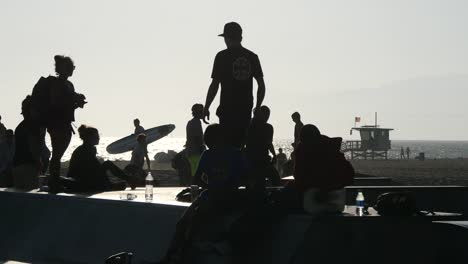 Los-Angeles-Venice-Beach-Young-Skateboarders-Backlit-With-Surfers-Beyond