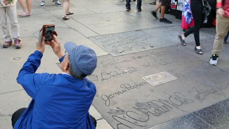 Los-Angeles-A-Tourist-Takes-A-Picture-By-Names-In-Concrete-On-The-Hollywood-Walk-Of-Fame