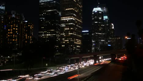 Los-Angeles-Looking-Down-At-Traffic-Passing-Skyscrapers-At-Night-Time-Lapse