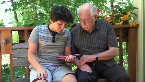 Boy-And-Grandfather-Discuss-Tablet-Use