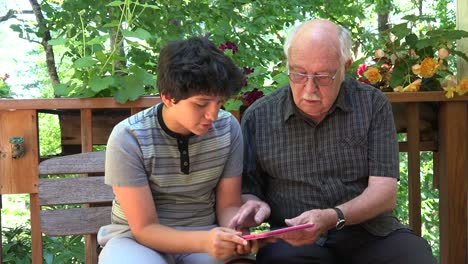 Boy-And-Grandfather-With-Pink-Tablet