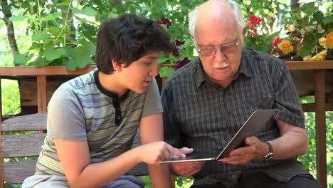 Boy-Explains-Computer-To-Grandfather