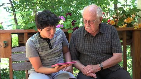 Boy-Explains-Tablet-Gestures-To-Grandfather