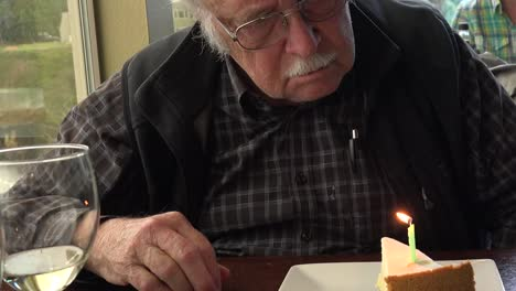 Old-Man-Looks-At-Birthday-Candle-Tilt