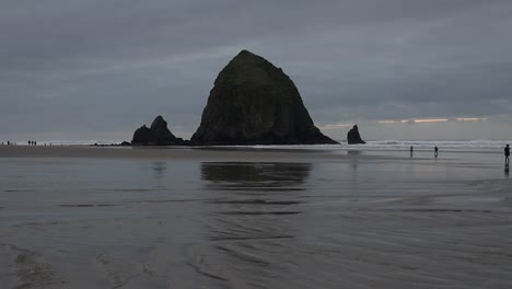 Oregon-Haystack-Rock-With-People-On-Beach