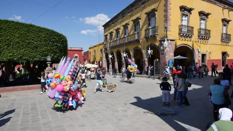 Mexico-San-Miguel-Balloon-Seller-And-Walking-Dog-In-A-Plaza