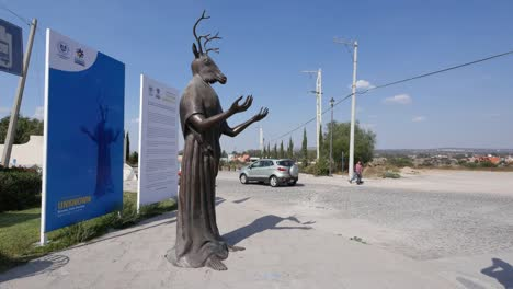 Mexico-San-Miguel-Statue-With-Deer-Head-With-People-And-Motor-Bike