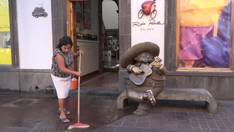 Mexico-Tlaquepaque-Woman-Sweeps-By-Statue