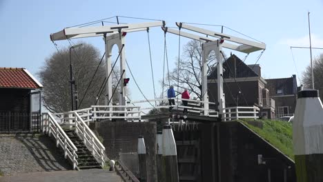 Netherlands-Schoonhoven-Three-People-Cross-Drawbridge