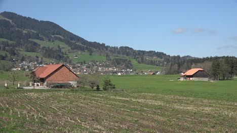 Switzerland-La-Gruyere-Farmhouses-And-Distant-Town-Zoom-In