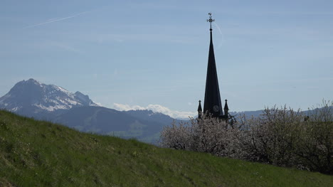 Switzerland-La-Gruyere-View-Of-Alps-Beyond-Church-Steeple