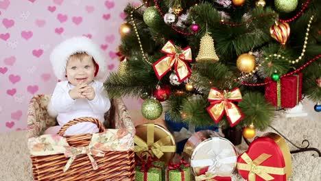 Baby-In-Weihnachtsmütze-Sitzt-In-Einem-Korb-Neben-Dem-Weihnachtsbaum-Und-Geschenken