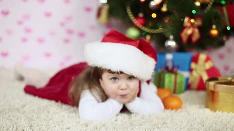 Babymädchen-In-Einer-Weihnachtsmütze-Auf-Dem-Teppich-Liegend-Zeitlupe