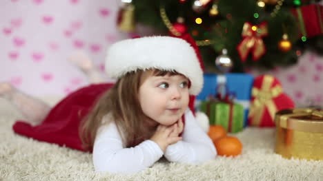 Baby-Girl-In-A-Santa-Hat-Lying-On-The-Floor-Looking-At-Camera-Slow-Motion