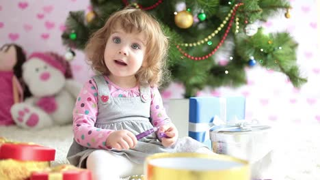 Baby-Girl-Shows-Tongue-And-Sitting-Beside-A-Christmas-Tree