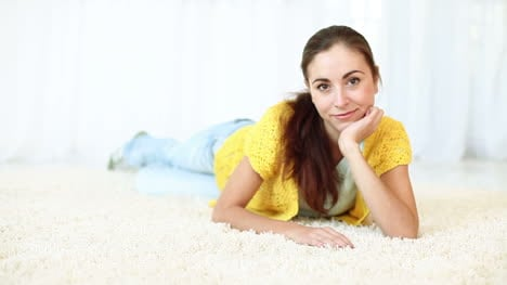 Beautiful-Young-Adult-Smiling-While-Lying-On-The-Carpet-Dolly-Hd