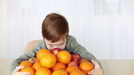 Boy-With-A-Lot-Of-Apples-And-Oranges