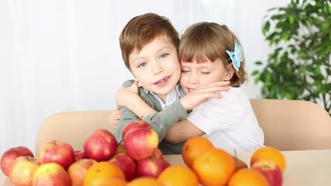 Brother-And-Sister-Hugging-They-Sit-At-The-Table-Fruit-On-The-Table