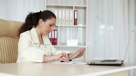 Business-woman-working-with-documents-near-laptop