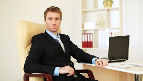 Businessman-Sitting-At-A-Desk-In-An-Office-Looking-At-The-Camera-Dolly-Hd