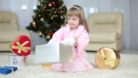 Child-Gets-A-Gift-From-The-Box-She-Sits-Beside-The-Christmas-Tree