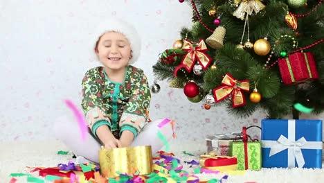 Kind-In-Weihnachtsmütze-Wirft-Konfetti-Und-Sitzt-Auf-Dem-Boden-In-Der-Nähe-Von-Weihnachten