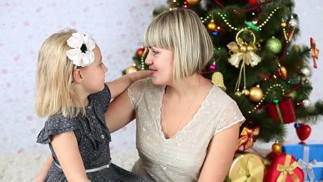 Tochter-Umarmt-Ihre-Mutter-Die-Neben-Einem-Weihnachtsbaum-Sitzt