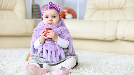 Girl-Child-Is-Sitting-On-The-Floor-Eating-An-Apple