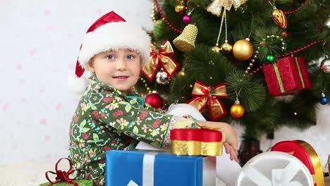 Mädchen-Mit-Weihnachtsmütze-Sitzt-Neben-Einem-Weihnachtsbaum