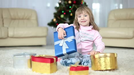 Girl-Is-Holding-A-Christmas-Gift-Sitting-Beside-A-Christmas-Tree