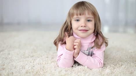 Mädchen-Das-Auf-Dem-Teppich-Liegt-Lächelt-Für-Die-Kamera