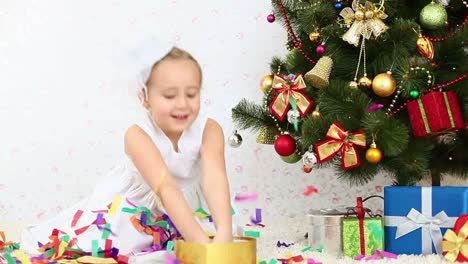 Girl-Tosses-Confetti-And-Sitting-On-The-Floor-Near-A-Christmas-Tree