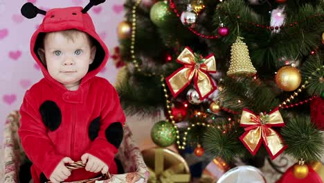 Happy-Baby-In-A-Basket-Near-The-Christmas-Tree-And-Gifts