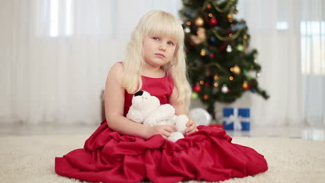 Happy-Child-Holding-A-Teddy-Bear-Beside-The-Christmas-Tree