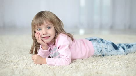 Happy-Child-Lying-On-A-Carpet-Looking-At-Camera