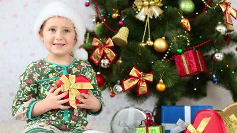 Glückliches-Mädchen-In-Weihnachtsmütze-Gibt-Ein-Geschenk
