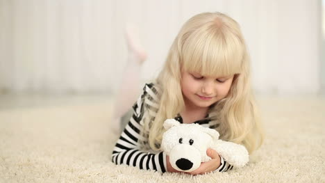 Happy-Girl-With-Teddy-Bear-Looking-At-Camera