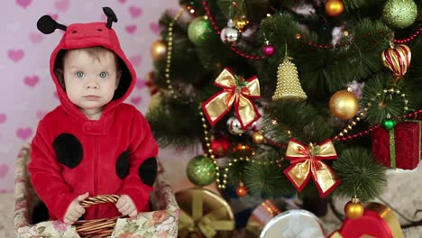 Happy-Kid-Nods-In-The-Basket-Near-The-Christmas-Tree-And-Gifts