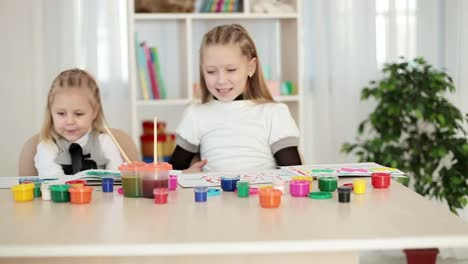 Happy-Kids-Are-Choosing-Paint-For-Painting-And-Looking-At-Camera