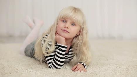 Happy-Little-Girl-Lying-On-The-Carpet