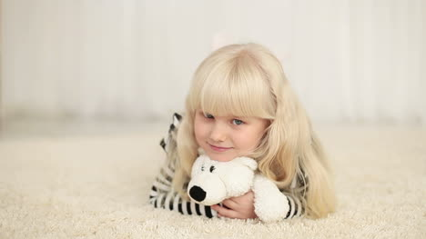 Happy-Little-Girl-Lying-With-Teddy-Bear-On-The-Carpet