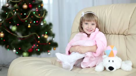 Happy-Little-Girl-Sitting-On-A-Couch-Near-The-Christmas-Tree