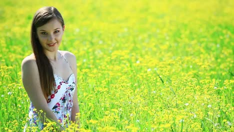 Happy-Young-Woman-With-Flowers-In-Grass-Look-At-Camera