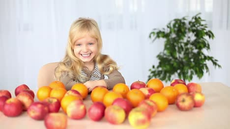 Laughing-Girl-At-The-Table-On-The-Table-Lay-Oranges-And-Apples