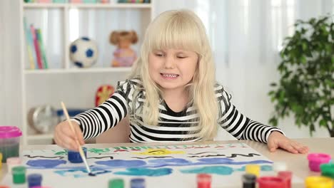 Little-Blonde-Girl-Paints-Pictures-On-A-Sheet-Of-Paper