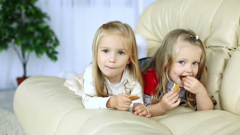 Little-Sisters-Lying-On-The-Couch-Eating-Cookies-Dolly-Hd
